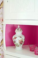 White corner cabinet with interior walls of shelf painted hot pink