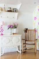 Wooden rocking chair next to vase of flowers on white, ornate cabinet