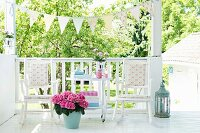 Pink hydrangeas in pot in front of rocking chairs and table on terrace with white rail and bunting