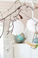 Glass ornaments and white baubles hanging from ornamental branch