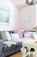 Grey leather couch with various scatter cushions with white coffee table in living room with walls painted pastel pink