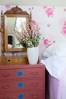 Vase of flowers and antique vanity mirror on mauve chest of drawers with pattern of blue flowers against floral wallpaper