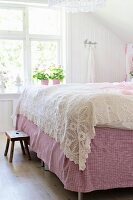 Crocheted, white bedspread on double bed in rustic bedroom