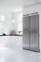 Black and white Scandinavian, country-house kitchen with side-by-side, stainless steel fridge-freezer