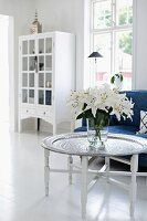 Vase on white lilies on tray table and blue sofa with white, glass-fronted cabinet in background
