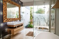 Partially visible bathtub in front of glazed shower area and view of terrace; washstand to one side below mirror with carved wooden frame on papered wall
