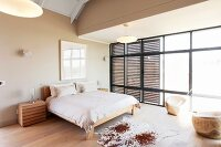 Animal-skin rug on fine wooden floor next to simple double bed in spacious bedroom with wooden, slatted sliding elements on glass wall