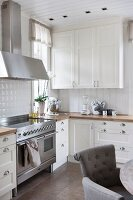 White country-house kitchen with stainless steel cooker and grey upholstered chair in foreground