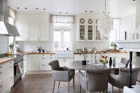 Comfortable dining area with grey upholstered chairs and oval dining table in white country-house kitchen
