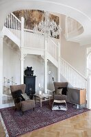 White staircase and balustrade in foyer of country-house villa; 50s armchair and side table on Oriental rug