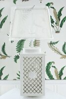 Table lamp with white ceramic base with ornate perforated pattern and translucent lampshade against fern-patterned wallpaper