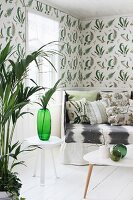 Indoor palm in living room with fern-patterned wallpaper
