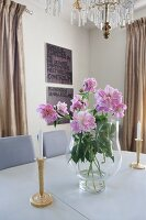 Vase of pink peonies between candlesticks on table