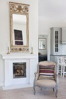 Striped scatter cushions on Rococo-style armchair in front of open fireplace with gilt-framed mirror on mantelpiece