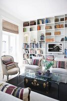 Striped scatter cushions on pale armchairs and Rococo armchair around curved glass table in front of fitted bookcases
