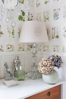 Table lamp with white lampshade and spherical vase of hydrangeas on chest of drawers against botanical wallpaper