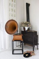 Old gramophone on side table in front of black iron stove in corner