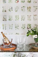Sparkling wine in wine cooler and glasses on console table against botanical wallpaper