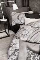White, retro bedside lamp on bedside table next to bed with grey-patterned bed linen