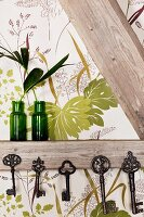 Collection of vintage keys hung from half-timber beams and green glass vases against leaf-patterned wallpaper