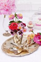 Silver cutlery & flower arrangement in shades of pink on silver tray