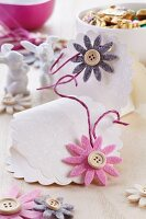 Hand-crafted bags made from embossed paper decorated with felt flowers and buttons for holding Easter treats