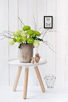 Chrysanthemums, viburnum and birch twigs in old stoneware jar on modern side table