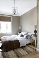 Bedroom in muted natural shades with many scatter cushions on bed, modern chandelier and antique-style bedside tables