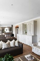 White, elegant, country-house-style dresser between seating area and dining area in open-plan interior