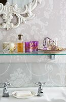 Ornate mirror frame, floral wallpaper and glass shelf of romantic knickknacks above vintage tap fittings