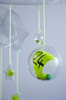 Number on green paper inside suspended plastic bauble