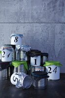 Hand-crafted Advent calender made from tin cans with tissue paper lids