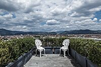 Two white, vintage, Rococo-style metal chairs positioned in corners of planted roof terrace with magnificent panoramic view