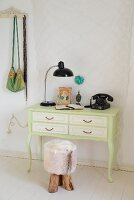 Miniature desk - writing desk painted pale green with vintage telephone, table lamp and rustic stool with fur cover on white board floor