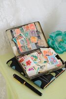 Postage stamps in old tin on notebook in retro 50s pattern, fountain pen and turquoise silk flower on table painted pale green
