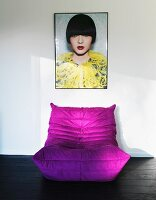 Purple beanbag on dark wooden floor below framed photo of woman on wall