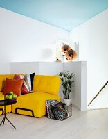 Yellow sofa with cushions next to wire basket, black metal side table, half-height white balustrade and stairs in background, pendant lamp hanging from pale blue ceiling
