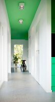 Light-flooded, white corridor with pale grey floor, black bar stool in background and spotlights on green-painted ceiling