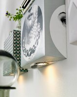 Homemade wall lights made from boxes and spotlights covered with various types of wallpaper