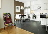 Retro chair with colourful upholstery in front of white kitchen-dining room with black accents and charcoal floor tiles