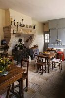 Rustic kitchen-dining room with wooden tables and chairs and antique wood-burning cooker in deep former fireplace