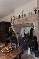 Rustic, French kitchen with antique wood-burning cooker in deep former fireplace and bowl of oranges on wooden table