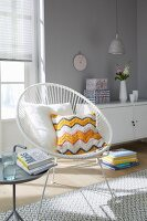A cushion with a crocheted cover on a white retro chair in front of a sideboard on a light grey wall