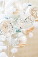 Silver Christmas baubles and small fluffy balls representing snowflakes