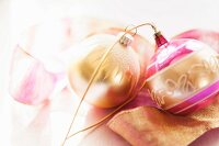 Gold and pink Christmas baubles lying on ribbon