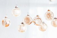 Row of suspended silver glass baubles with embossed patterns in convex sides