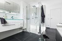 A long wash stand built into a white unit with a multi-door, mirrored cabinet and an illuminated glass shelf above it and a glass shower cubicle in the background in modern, black-and-white bathroom with large black floor tiles
