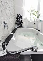 A bubble jet bathtub with underwater illumination filled with water against a natural stone wall showing a contrast between smooth and rough materials with a message in the background made from black letters
