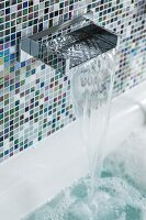 An elegant waterfall tap on a wall with shimmering blue-and-white mosaic tiles with the water running into a bubble bath