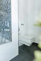 A square modern toilet installed discreetly in a corner behind the bathtub